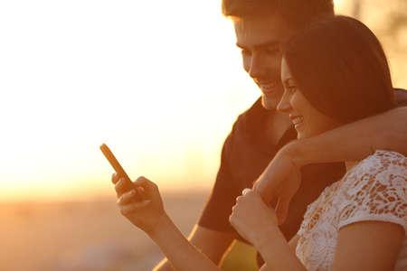 ragazza innamorata: Coppia felice utilizzando uno smartphone in un tramonto luminoso posteriore sulla spiaggia