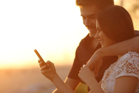 Happy couple using a smartphone in a sunset back light on the beach