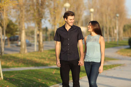 walk in: Happy couple laughing while taking a walk in a park Stock Photo