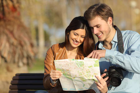destination wedding: Happy tourists searching landmarks in a map sitting on a bench outdoors