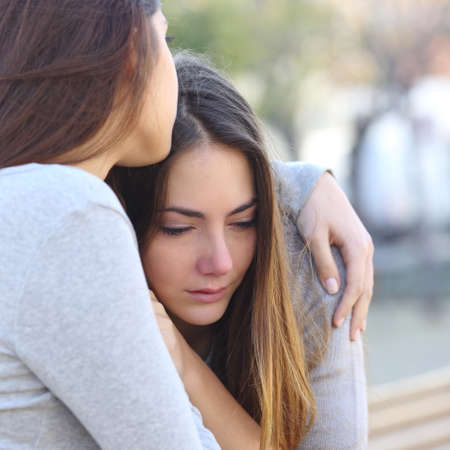 Sad girl crying and a friend comforting her outdoors in a park Banque d'images