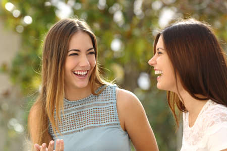 attractive female: Happy women talking and laughing in a park with a green background