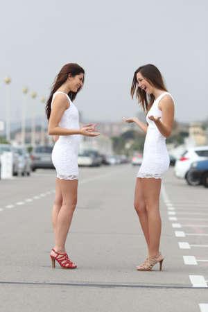 actitud: Las mujeres de moda felices, vistiendo el mismo vestido y mirando sorprendido Foto de archivo