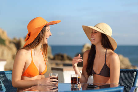 Two friends talking in an hotel terrace on holidays with the beach in the background Stock Photo