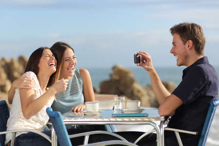 Friends on vacations laughing and taking photo with a smart phone in a restaurant on the beach Foto de archivo
