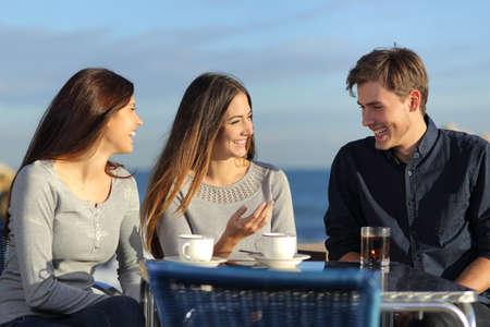 화창한 날에 해변에있는 식당 테라스에서 얘기하는 친구