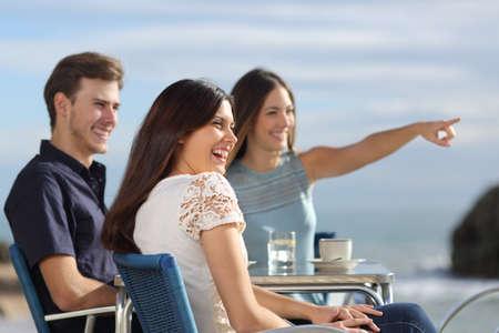 mujer mirando el horizonte: Grupo de amigos riendo y mirando al horizonte en un restaurante en la playa con el mar de fondo