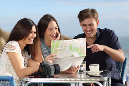 student travel: Group of young tourist friends consulting a paper map in a restaurant with the beach in the background