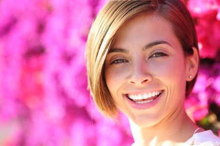 Mooie vrouw lachend met witte perfecte tanden met een warmte veel van roze bloemen op de achtergrond