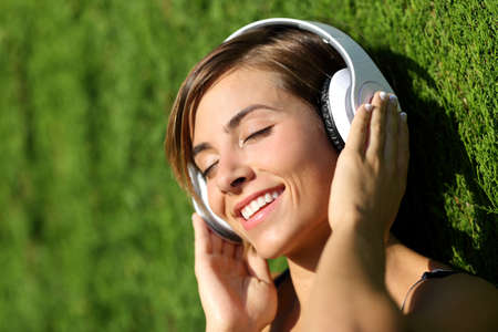 listening device: Happy girl listening to the music with headphones in a park with a green blurred background