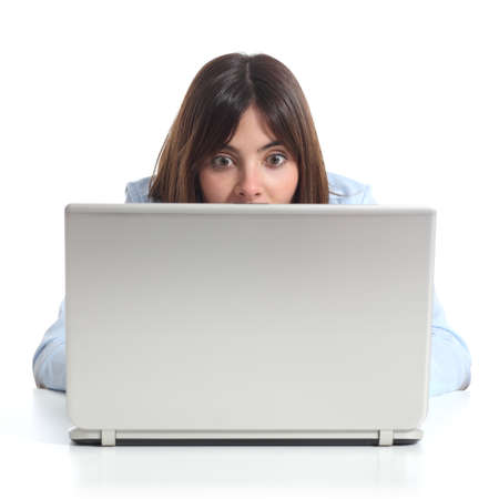 Upset woman watching a laptop isolated on a white background 스톡 콘텐츠