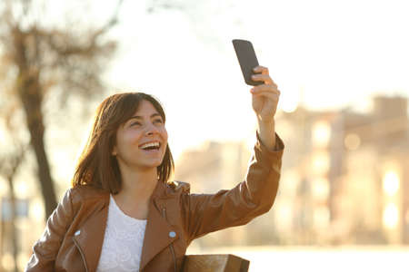 Woman taking selfie photo with a smarphone in winter sitting in a bench in a park photo