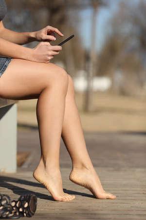piernas con tacones: Mujer que usa un teléfono elegante que se relaja en un parque descalzo con un fondo desenfocado Foto de archivo