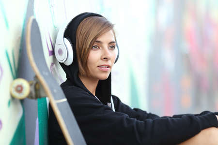 listening device: Young skater girl listening to the music with headphones with a blurred graffiti wall in the background