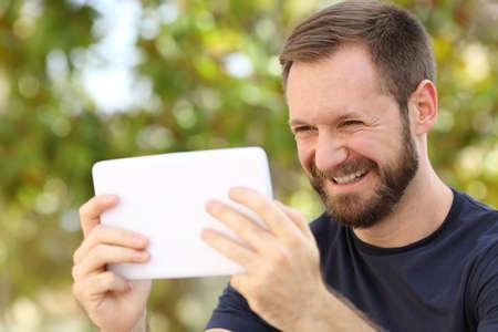 jugando videojuegos: Hombre feliz viendo videos en una tableta ereader en un parque con un fondo verde