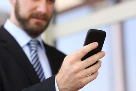 executive: Executive hand using a smartphone in the street with an office building in the background