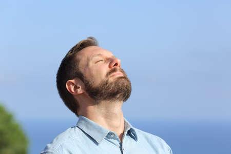 Man ademen diep frisse lucht buiten met een blauwe lucht op de achtergrond