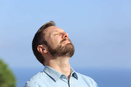 Man breathing deep fresh air outdoors with a blue sky in the background Stock Photo