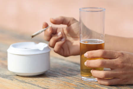 Woman hands holding a cigarette smoking and drinking alcohol in a bar table Imagens
