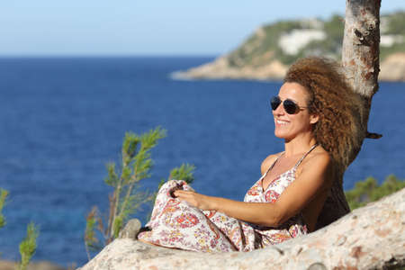 Tourist woman relaxing on the beach in vacations sitting on a tree with the ocean in the background