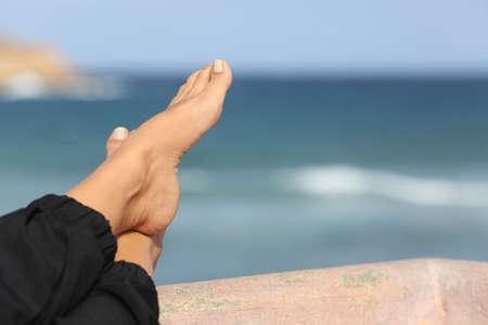 Close-up van een vrouw voeten ontspannen op een hotel op het strand terras met de zee op de achtergrond