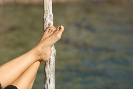 adult's feet: Woman feet relaxing on holidays in a beach or lake with the sea water in the background