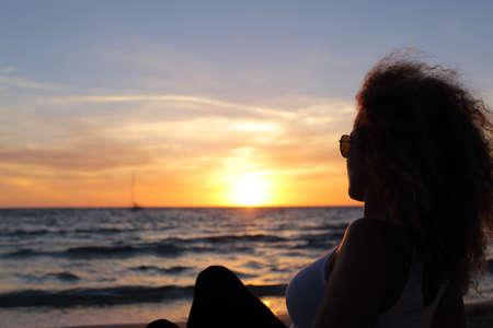 mujer mirando el horizonte: Volver la vista de una silueta mujer viendo una puesta de sol en la playa de Ibiza Foto de archivo