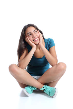 Teenager girl sitting and thinking looking sideways isolated on a white background