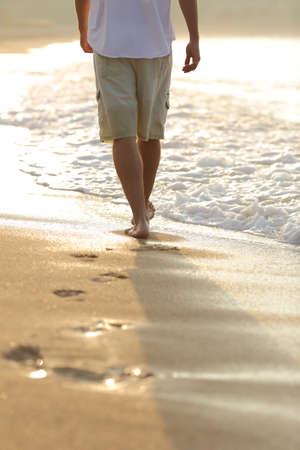 Podsvícení muže nohy chůzi na pláži opuštění stopy