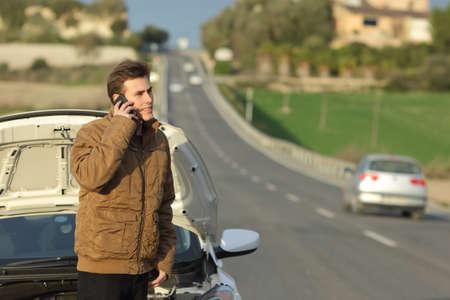 幸せな男彼の故障車は国の道路の道端での援助を呼び出す