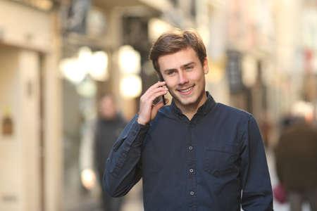 person calling: Vista frontal de un hombre feliz llamando en el tel�fono caminar en la calle