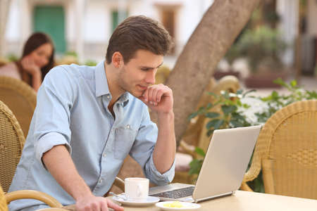 self study: Self employed man concentrated while is working with a laptop in a restaurant terrace Stock Photo