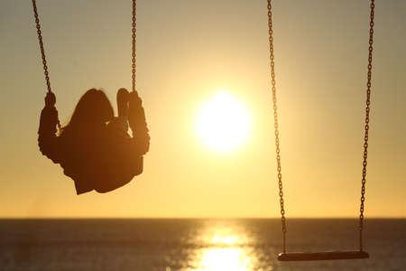 다른 빈 스윙 해변에서 석양 외로운 여자 실루엣 스윙의 백라이트