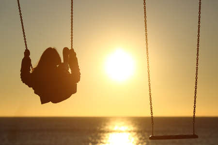 mujer mirando el horizonte: Luz posterior de una mujer solitaria silueta swinging al atardecer en la playa con otro columpio vac�o