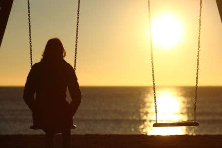 mujer pensativa: Mujer sola viendo la puesta de sol solo en invierno en la playa al atardecer Foto de archivo