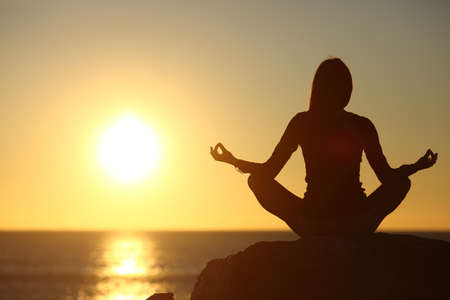 Woman meditating and practicing yoga watching the sun on the beach at sunset Standard-Bild