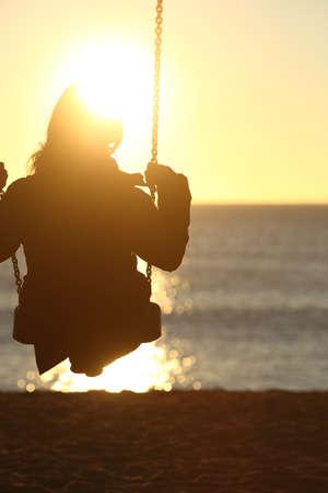 Vrouw silhouet swingende bij zonsondergang op het strand en kijken naar de zon