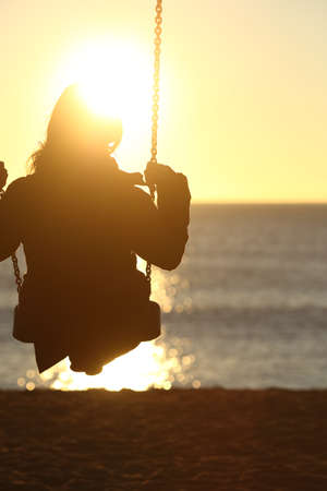 Woman silhouette swinging at sunset on the beach and watching the sun