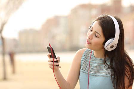 cantando: Canto divertido muchacha adolescente y escuchar música desde un teléfono inteligente con auriculares en un parque urbano