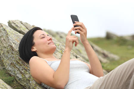 Happy woman using a mobile phone lying in the mountain with a white isolated sky in the background photo