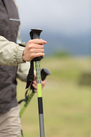 walking pole: Close up of a hiker hands holding a hiking pole while walking in the mountain