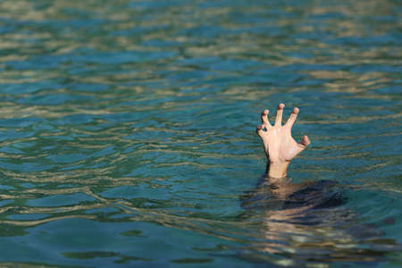 drowning: Man hand drowning in the ocean in a sunny day Stock Photo
