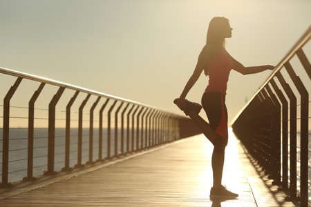 copy: Woman silhouette exercising stretching on a bridge after running at sunset