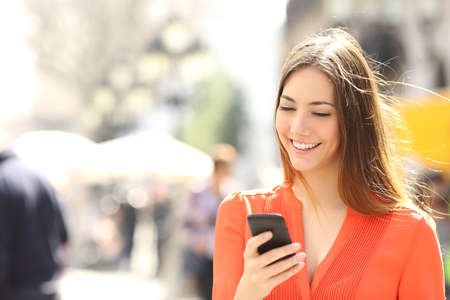 Woman wearing orange shirt texting on the smart phone walking in the street in a sunny day