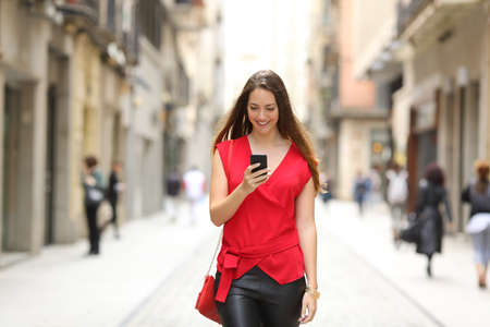 chicas sonriendo: Vista frontal de una forma feliz mujer caminando y usando un teléfono inteligente en una calle de la ciudad