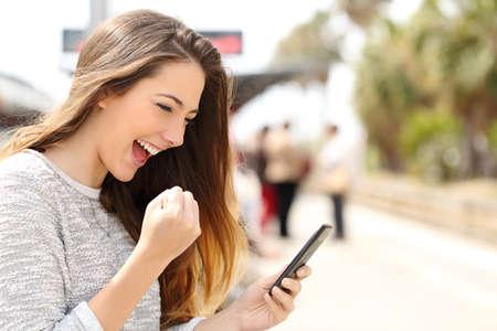 puesto de trabajo: Mujer eufórico de ver su teléfono inteligente en un rato estación de tren está a la espera
