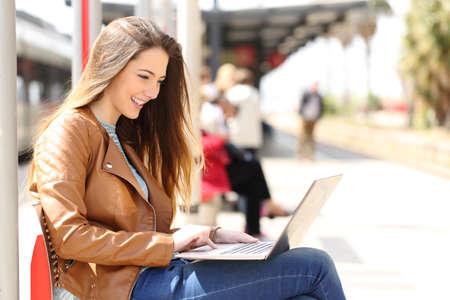 Zijaanzicht van een meisje met behulp van een laptop tijdens het wachten in een treinstation in een zonnige dag Stockfoto