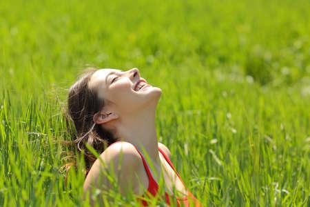新鮮な空気を呼吸し、夏の晴れた日に牧草地で日光浴を楽しむ幸せな女の子顔