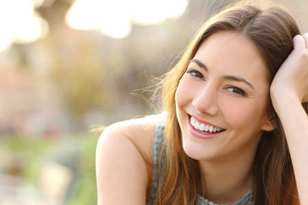 dentisterie: Femme souriante avec un sourire parfait et dents blanches dans un parc et en regardant la caméra