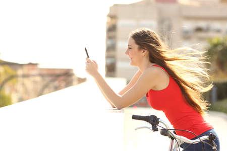profil: Profil Dziewczyna nastolatka przy użyciu telefonu komórkowego w parku w słoneczny letni dzień z wiatrem włosy w ruchu